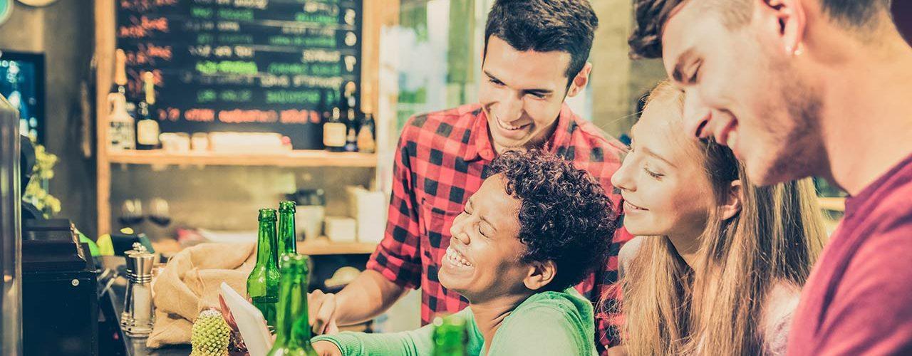 Happy students enjoying a drink in a bar